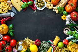 Italian food ingredients. Vegetables, olive oil, cheese, herbs and pasta on dark background