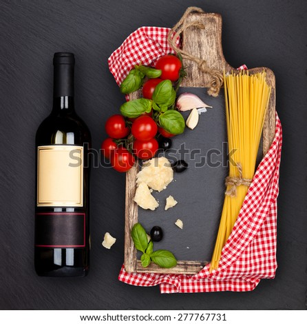 Italian Food. Italian pasta ingredients and bottle of wine on black slate board.