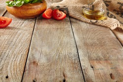 Italian Food on Old Wooden Background with Selective Focus. Table Top Perspective with Tomatoes, Basil and Olive Oil with Place for Text. Blurred Vintage Aged Boards Texture