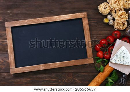 Italian food on vintage wood background with chalkboard with copyspace