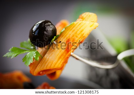Stock Photo Italian food. Pasta penne with tomato sauce, olives and garnish