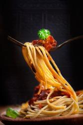 Italian food. Pasta spaghetti with tomato sauce, olives and garnish. Pasta macro on fork