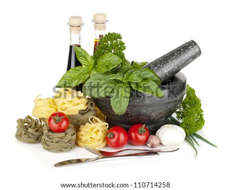 Italian food: pasta, tomatoes, herbs in mortar. Isolated on white background