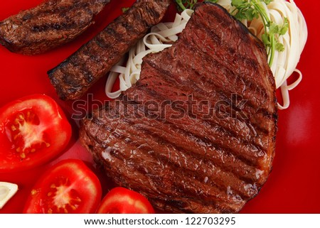 italian food : pasta with tomato and grilled sirloin beef on red plate isolated over white background