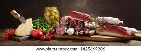 Italian food. Various kind types of salami, speck, sausages, parmesan cheese, green olives, basil and fresh tomatoes on a wooden table