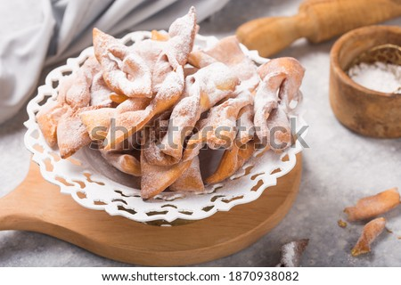 Italian Frappe or chiacchiere (hvorost) - typical Italian carnival fritters dusted with powdered sugar on concrete  table.