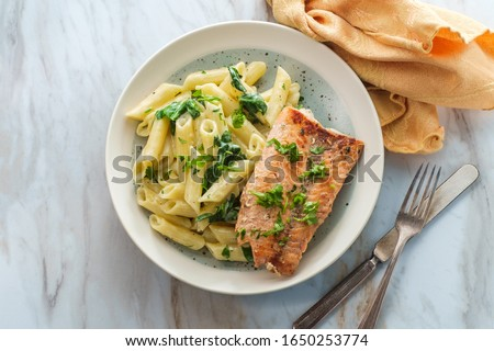 Italian fried salmon and penne rigate with creamy spinach alfredo pasta sauce ストックフォト ©