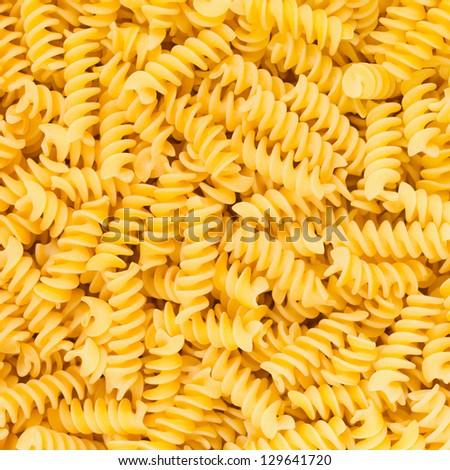 Italian Fusilli or Rotini helix shaped Macaroni Pasta raw food background or texture close up
