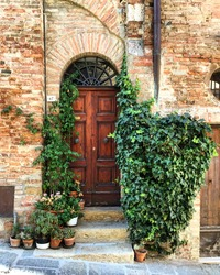 Italian house. Facade decorated with flowers and ivy. Wooden door. Photo made in Toscana.