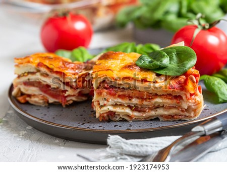 Italian lasagna with tomato sauce and cheese served with tomatoes and spinach, light concrete background. Homemade vegetarian lasagna. Selective focus.