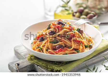 Italian lunch. Spaghetti alla puttanesca - italian pasta dish with tomatoes, olives, capers and parsley. Light background. Copy space. Foto stock ©