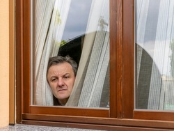 Italian man forced to remain in quarantine because of the coronavirus covid-19 peeps through the window with a disconsolate expression