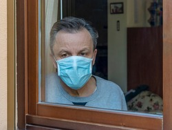 Italian man with protective mask, forced to stay at home due to coronavirus covid-19, disconsolate looks out the window of the house
