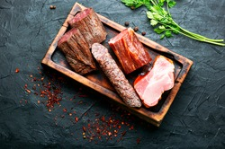 Italian meat platter.Cured meat and sausages on kitchen board
