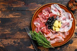 Italian meat platter with prosciutto ham, bresaola, pancetta, salami and parmesan. Dark wooden background. Top view. Copy space