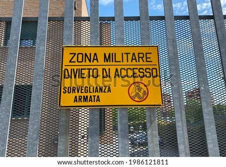 Italian military area with yellow sign: 'Military zone, no entry, armed surveillance'. Translation in Italian language: 'Zona militare, divieto di accesso, sorveglianza armata'. Foto stock ©