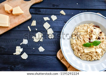 Italian mushroom risotto with parmesan cheese and fresh basil on rustic background