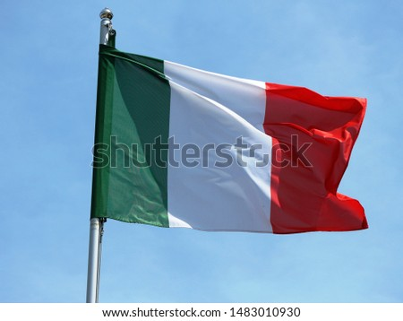 italian national flag waving on the wind in the blue sky #1483010930