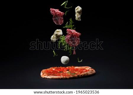 Italian Neapolitan pizza on the black background, sourdough bottom, tomato sauce Marinara with ingredients Jamon  Prosciutto dry-cured ham mozzarella and Arugula falling down on pizza