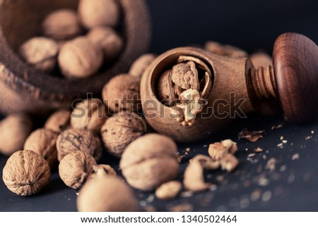 Italian nuts. Wooden nutcracker. Scattered nuts on a table with shallow depth of depth and depth. #1340502464