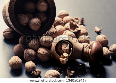 Italian nuts. Wooden nutcracker. Scattered nuts on a table with shallow depth of depth and depth. #1340502467