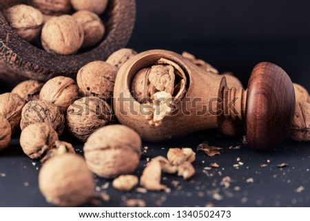 Italian nuts. Wooden nutcracker. Scattered nuts on a table with shallow depth of depth and depth. #1340502473