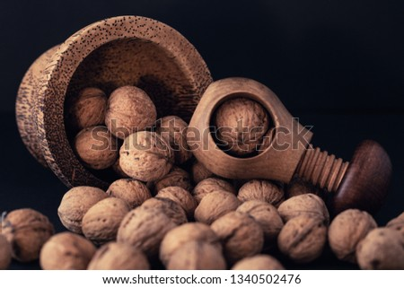 Italian nuts. Wooden nutcracker. Scattered nuts on a table with shallow depth of depth and depth. #1340502476