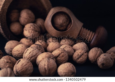 Italian nuts. Wooden nutcracker. Scattered nuts on a table with shallow depth of depth and depth. #1340502479
