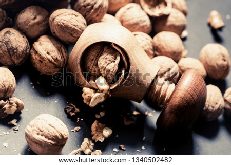 Italian nuts. Wooden nutcracker. Scattered nuts on a table with shallow depth of depth and depth. #1340502482