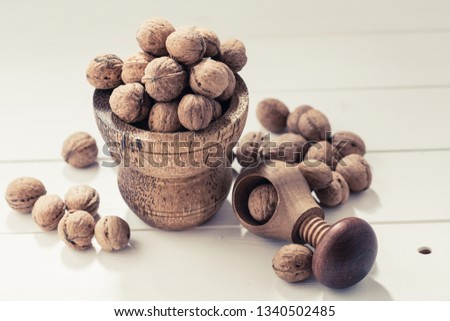 Italian nuts. Wooden nutcracker. Scattered nuts on a table with shallow depth of depth and depth. #1340502485
