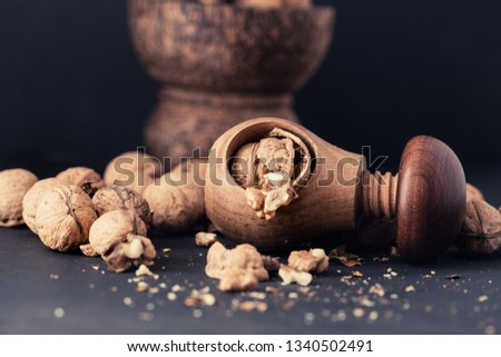 Italian nuts. Wooden nutcracker. Scattered nuts on a table with shallow depth of depth and depth. #1340502491