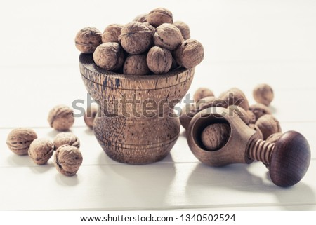 Italian nuts. Wooden nutcracker. Scattered nuts on a table with shallow depth of depth and depth. #1340502524