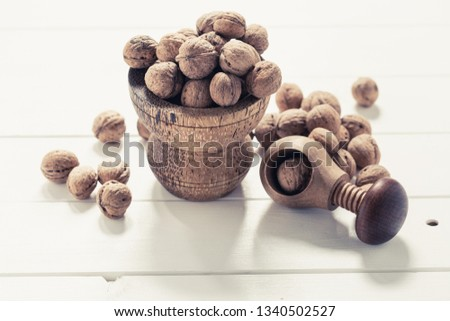 Italian nuts. Wooden nutcracker. Scattered nuts on a table with shallow depth of depth and depth. #1340502527