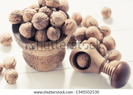 Italian nuts. Wooden nutcracker. Scattered nuts on a table with shallow depth of depth and depth. #1340502530