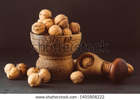 Italian nuts. Wooden nutcracker. Scattered nuts on a table with shallow depth of depth and depth. #1405808222