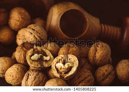Italian nuts. Wooden nutcracker. Scattered nuts on a table with shallow depth of depth and depth. #1405808225