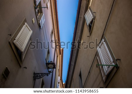 Italian old city narrow back street alley way district  from below with closed windows and bright blue sky background between buildings