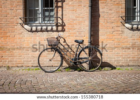 Italian old-style bicycles leaning against a wall in the historic centreof Ferrara