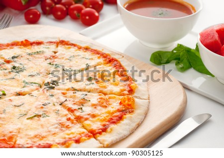 Italian original thin crust pizza Margherita with gazpacho soup and watermelon on side,and vegetables on background