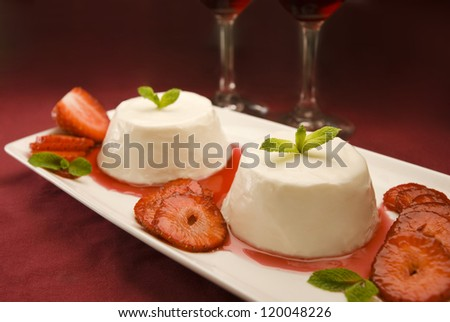 Italian panna cotta dessert garnished with fresh mint, strawberries and syrup