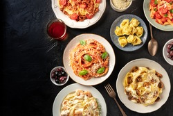 Italian pasta banner design template with copy space. A flat lay of an assortment of pasta dishes with wine and olives, shot from the top on a dark background with a place for text
