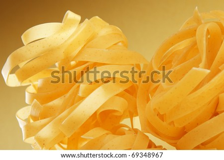 Italian pasta close-up on yellow gradient surface.
