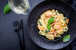 Italian pasta fettuccine in a creamy sauce with shrimp on a black plate, top view