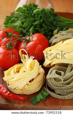 Italian pasta, olive oil and tomatoes on  vintage background