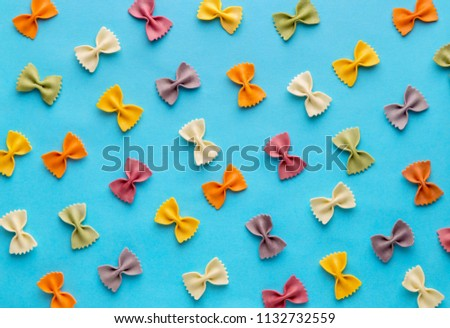 Italian pasta pattern on a blue background. Various colors of bow tie farfalle pasta viewed from above. Top view. Repetition. Full frame