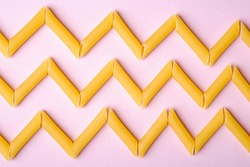 Italian pasta, raw penne tube macaroni zigzag pattern on pink background, top view, abstract food