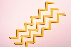 Italian pasta, raw penne tube macaroni zigzag pattern on pink background, top view copy space, abstract food