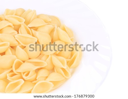 Italian pasta shells on a white plate. isolated on white background
