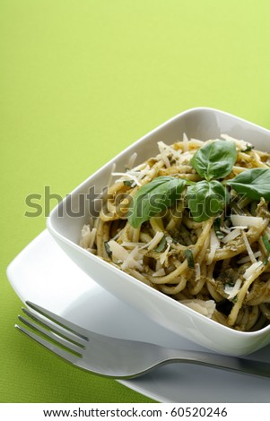 Italian pasta with pesto sause and parmesan and fork.