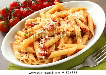 Italian pasta with sauce and parmesan cheese, served on a white oval plate